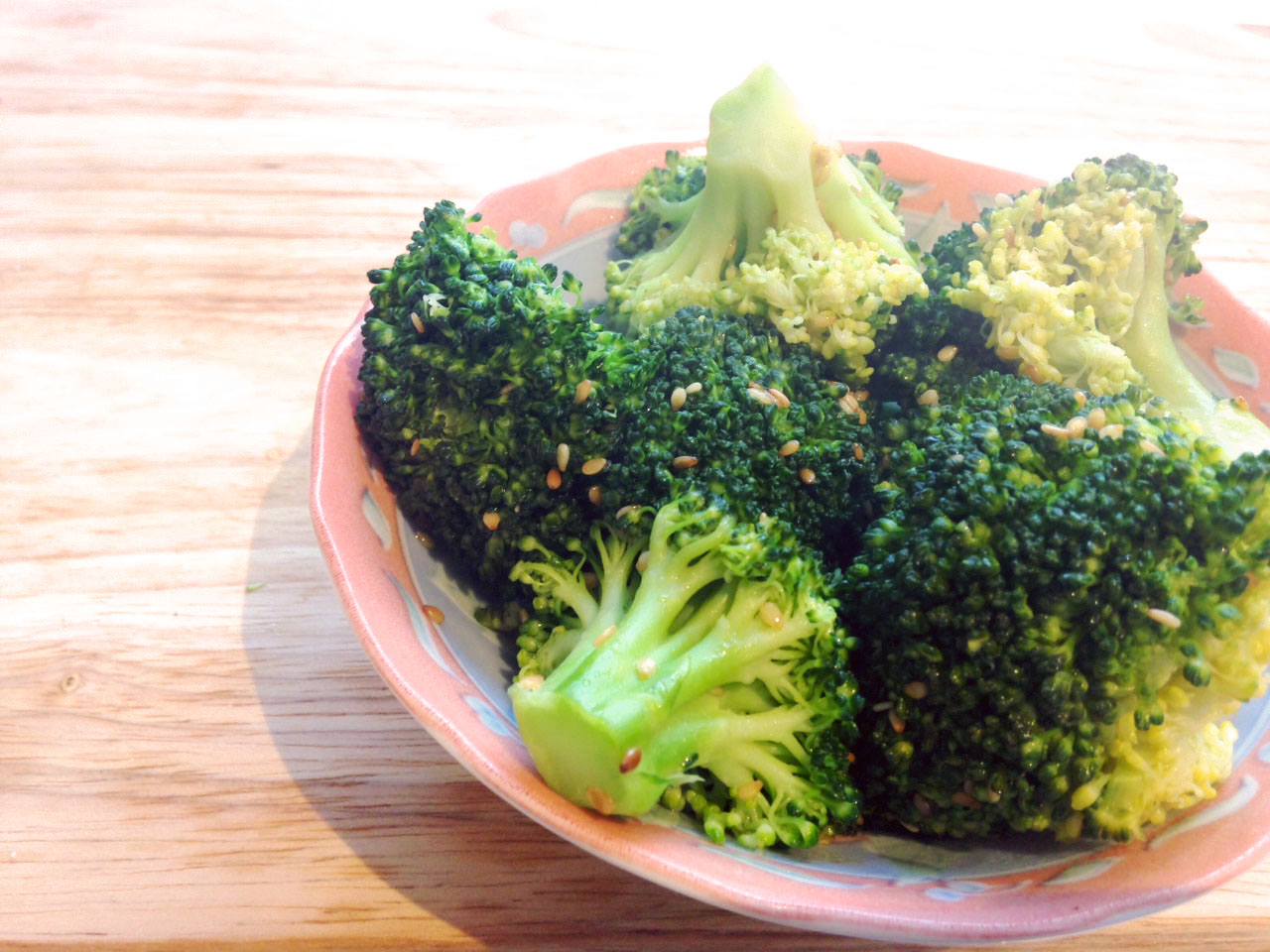 broccoli with sesame seeds in a bowl in wooden table