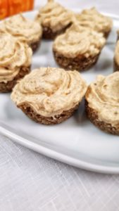 Pumpkin Spice Cheesecake bites on a white plate, on a white tablecloth with pumpkin in background