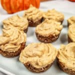 pumpkin spice cheesecake bites on white plate with pumpkins in background