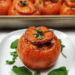 stuffed greek tomato on plate with fresh herbs, tray of tomatoes in background