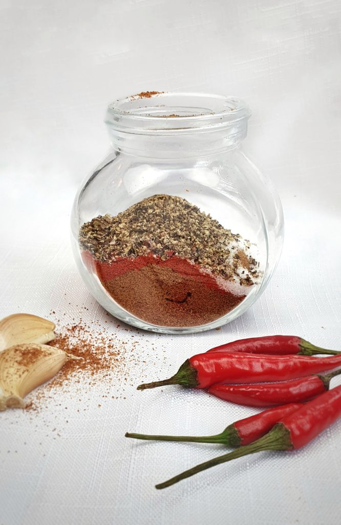 taco seasoning in jar on white table with chili peppers and garlic