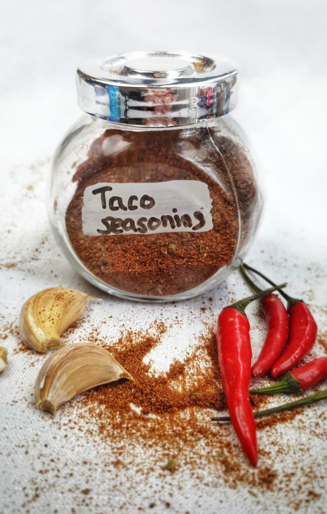 taco seasoning in jar on white table with spilled spice mix, garlic and chili peppers