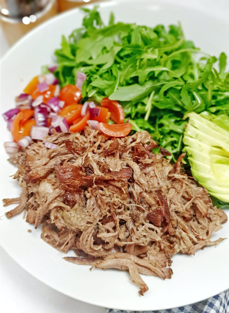 crispy carnitas on white plate with arugula, tomatoes and onions