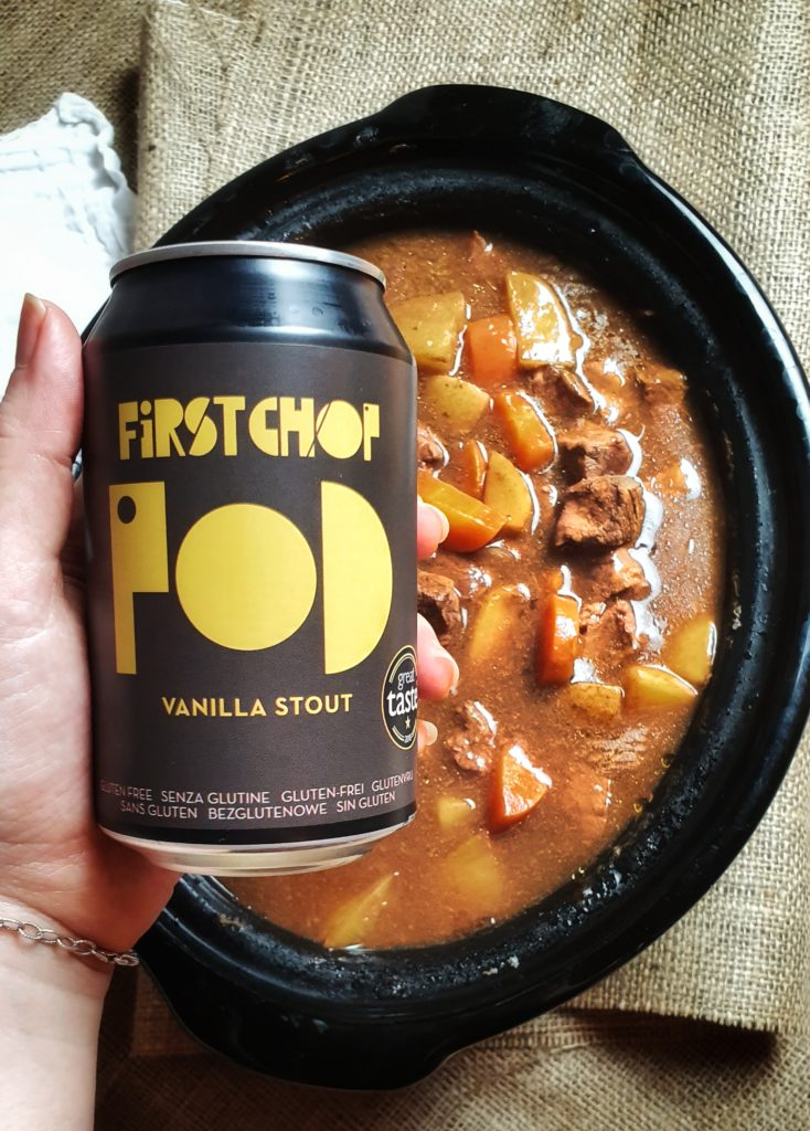 hand holding Firstchop stout beer over crockpot