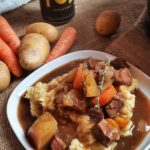 beef stew on plate with parsnip chili puree, firstchop beer in background with potatoes, carrots and slow cooker