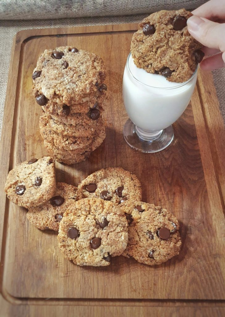 Chocolate chip cookies on wooden board with glass of almond milk, one cookies being dipped into milk