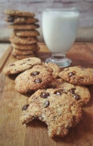 Chocolate chip cookies on wooden board with glass of almond milk