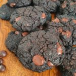 Double Chocolate Cookies on wooden chopping board with glass of milk