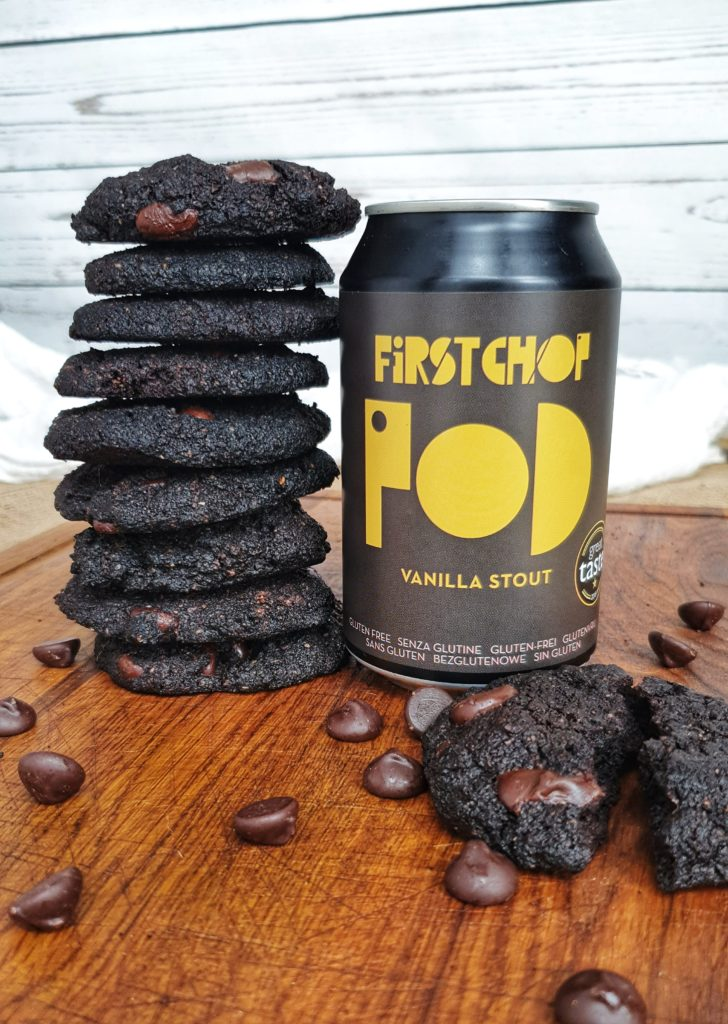 pile of chocolate cookies next to can of first chop pod stout on wooden table with chocolate chips