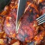 knife cutting bbq chicken in half