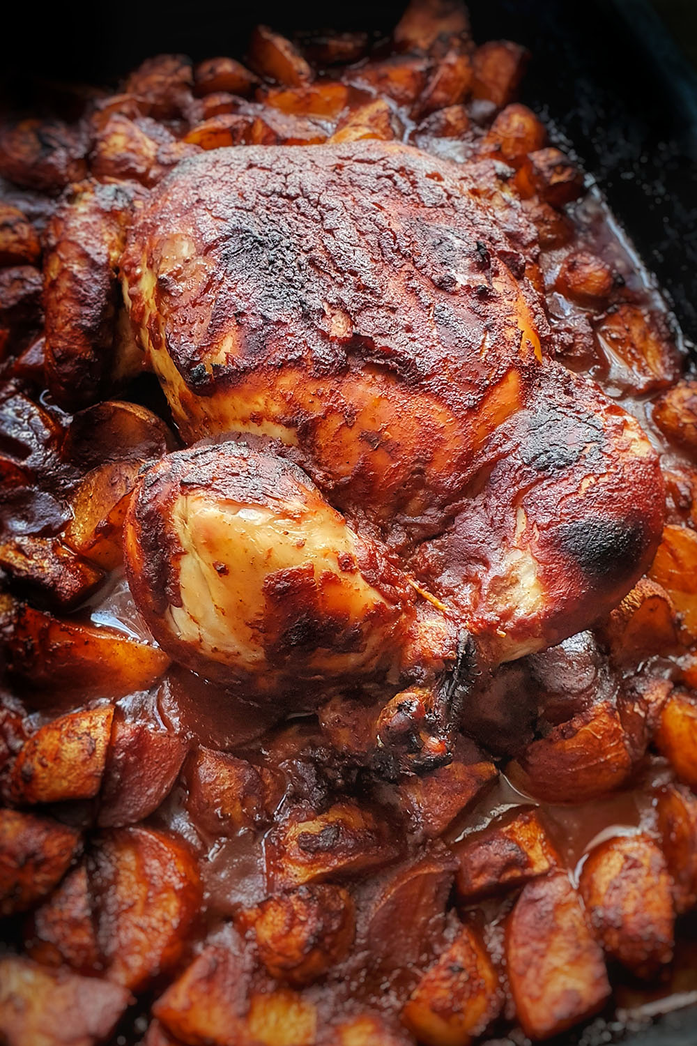 side shot of bbq chicken in pan with potatoes