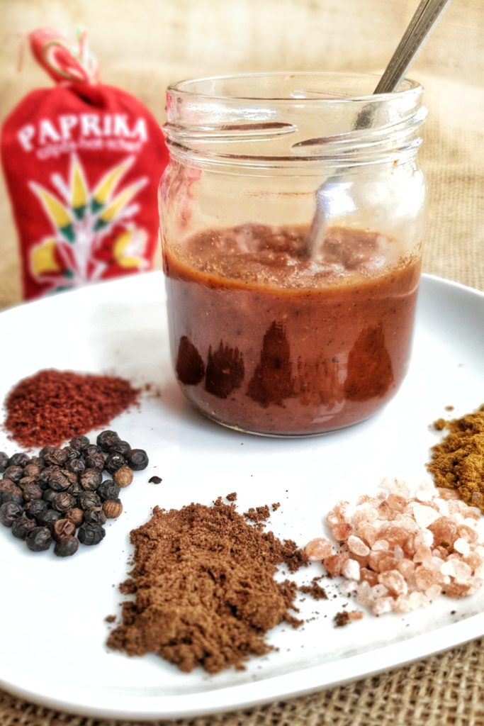 Side view of sumac bbq sauce surrounded by spices
