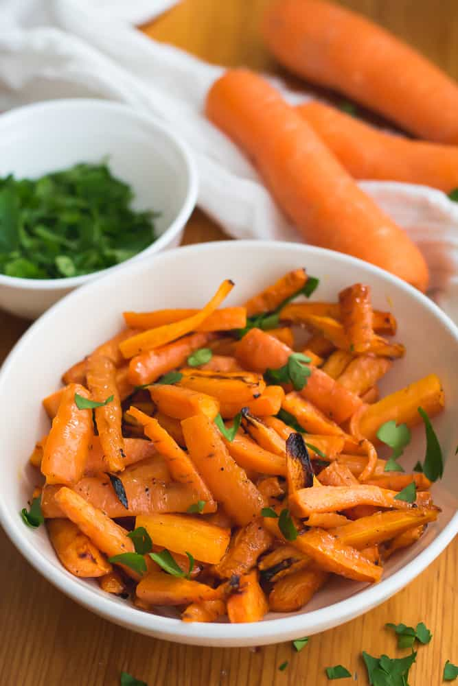 air fryer carrots in white bowl with parsley and carrots in background