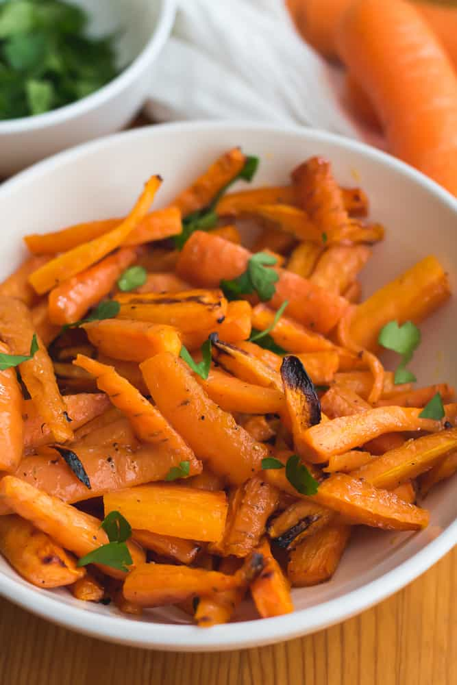 close up 45 degree angle air fryer carrots in white bowl next to bowl of parsley and carrots