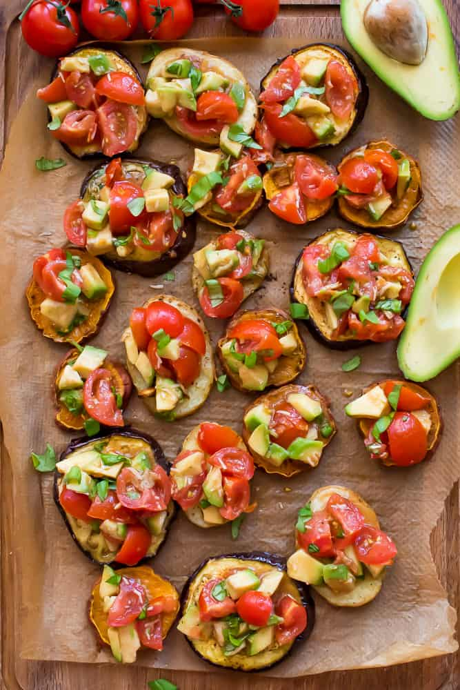 lots of avocado bruschetta on parchment paper surrounded by avocado and tomatoes