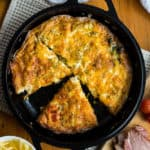 ham and cheese frittata in cast iron skillet on wooden table, overhead