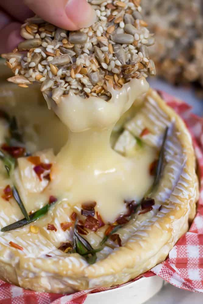 side shot of baked camembert with honey, rosemary and chilies, oozing off of a cracker.