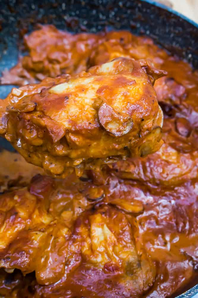 spoon lifting chicken thigh covered in stroganoff sauce