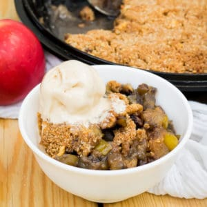white bowl of keto apple crisp with ice cream on top, in front of cast-iron and an apple