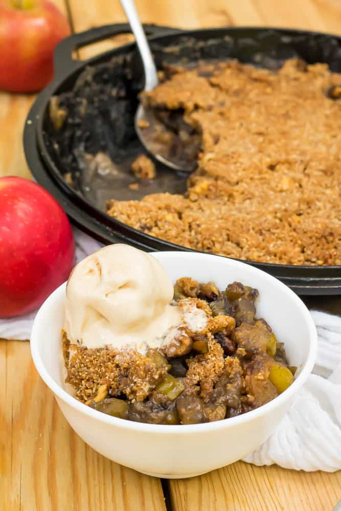 keto apple crisp in a white bowl with scoop of salted caramel ice cream on top, in front of an apple and a cast iron skillet with apple crisp inside