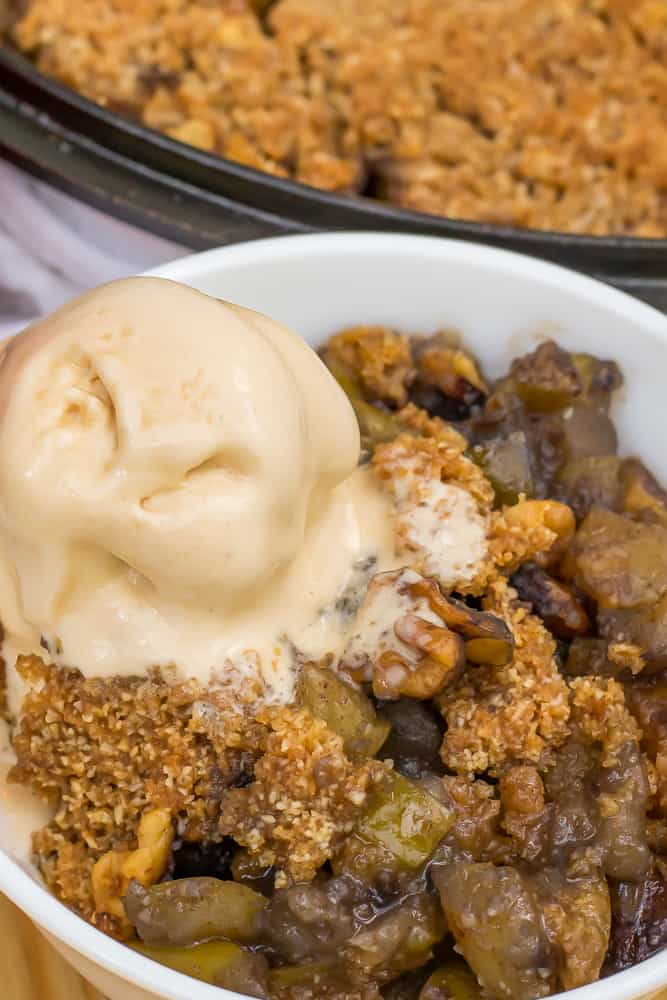 keto apple crisp in a white bowl with scoop of salted caramel ice cream on top, in front of a cast iron skillet with apple crisp inside