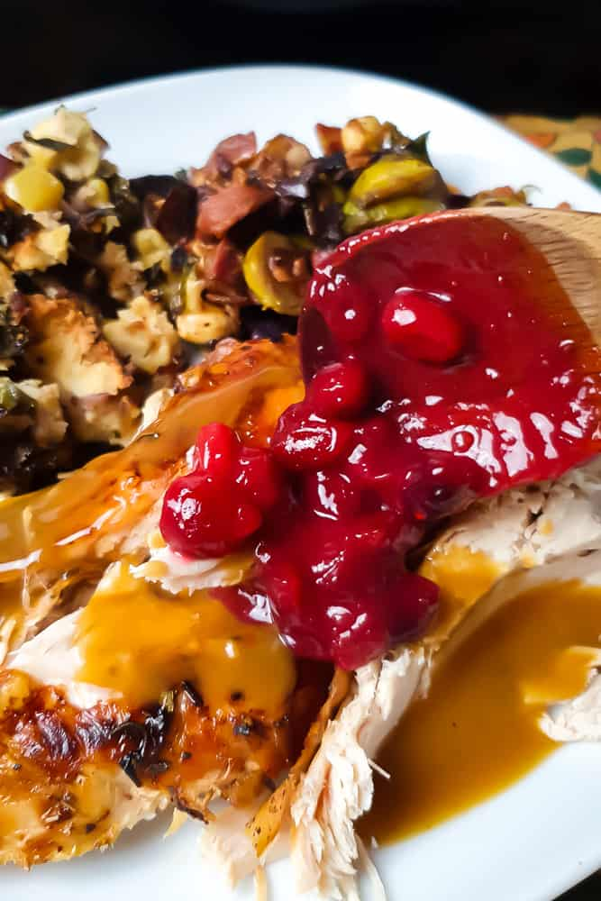 a wooden spoon spooning keto cranberry sauce over turkey on a thanksgiving plate