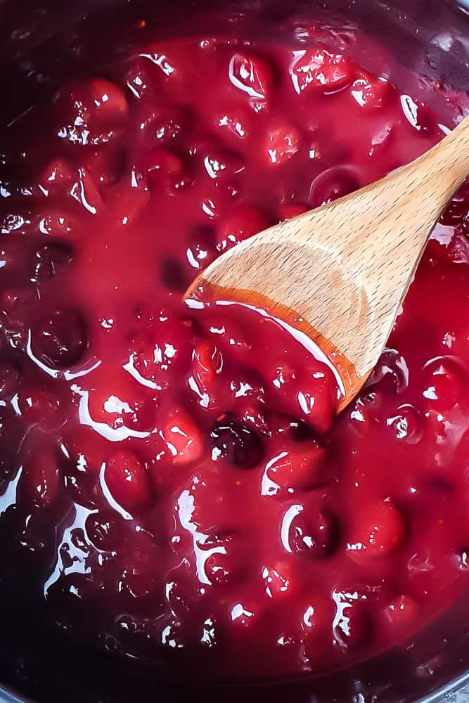 keto cranberry sauce in a pot with a wooden spoon
